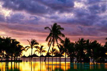 Pool and palm trees silhouetted against Mauritius sunset